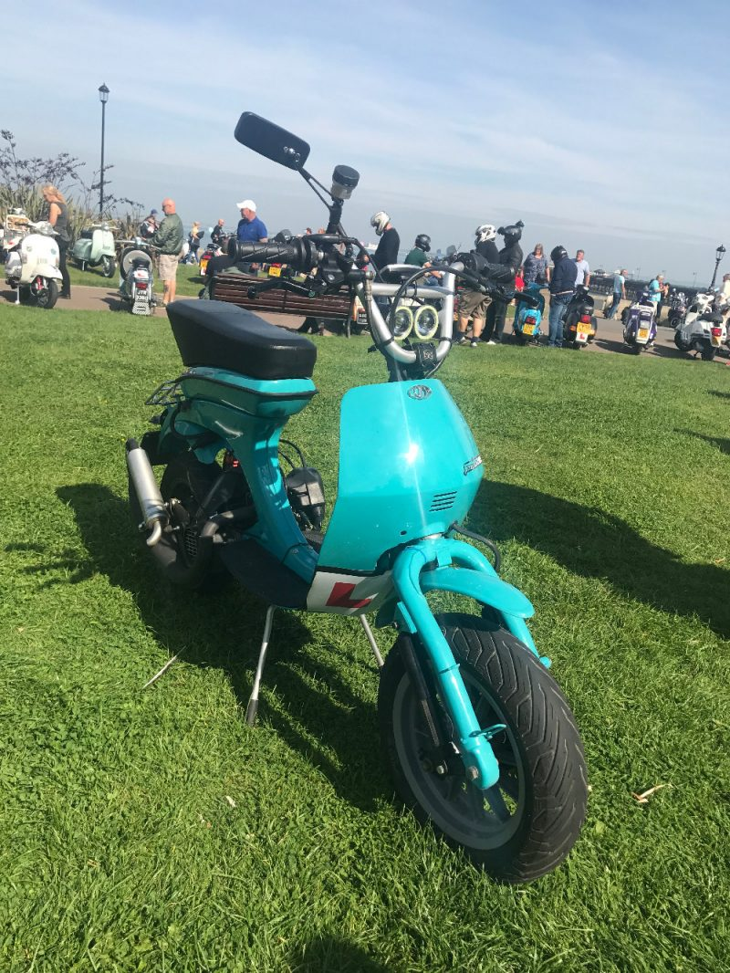 A turquoise Lambretta Vega parked on the green grass on Ryde seafront