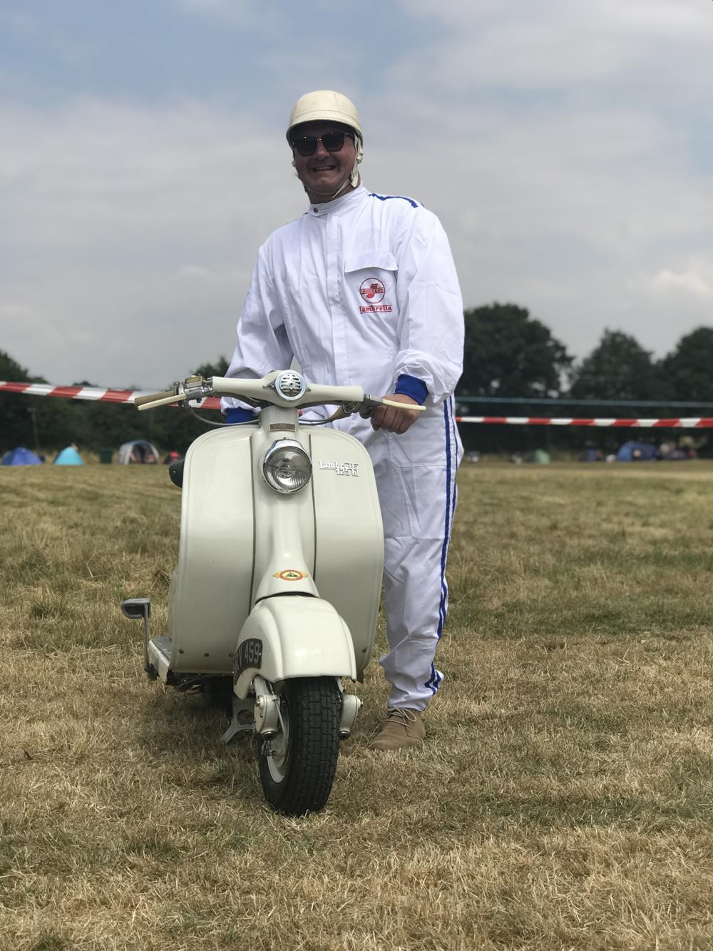 Scooter rider in white overalls next to a Vintage Lambretta LD