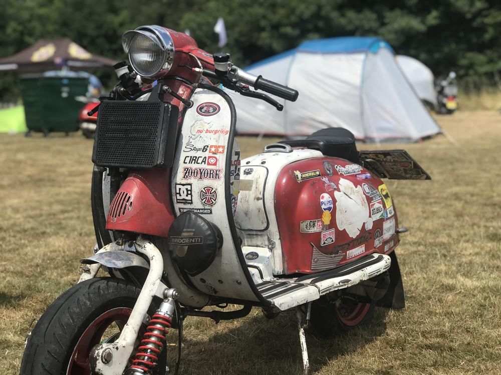 Red and white Lambretta with stickers and a radiator on the front fairings