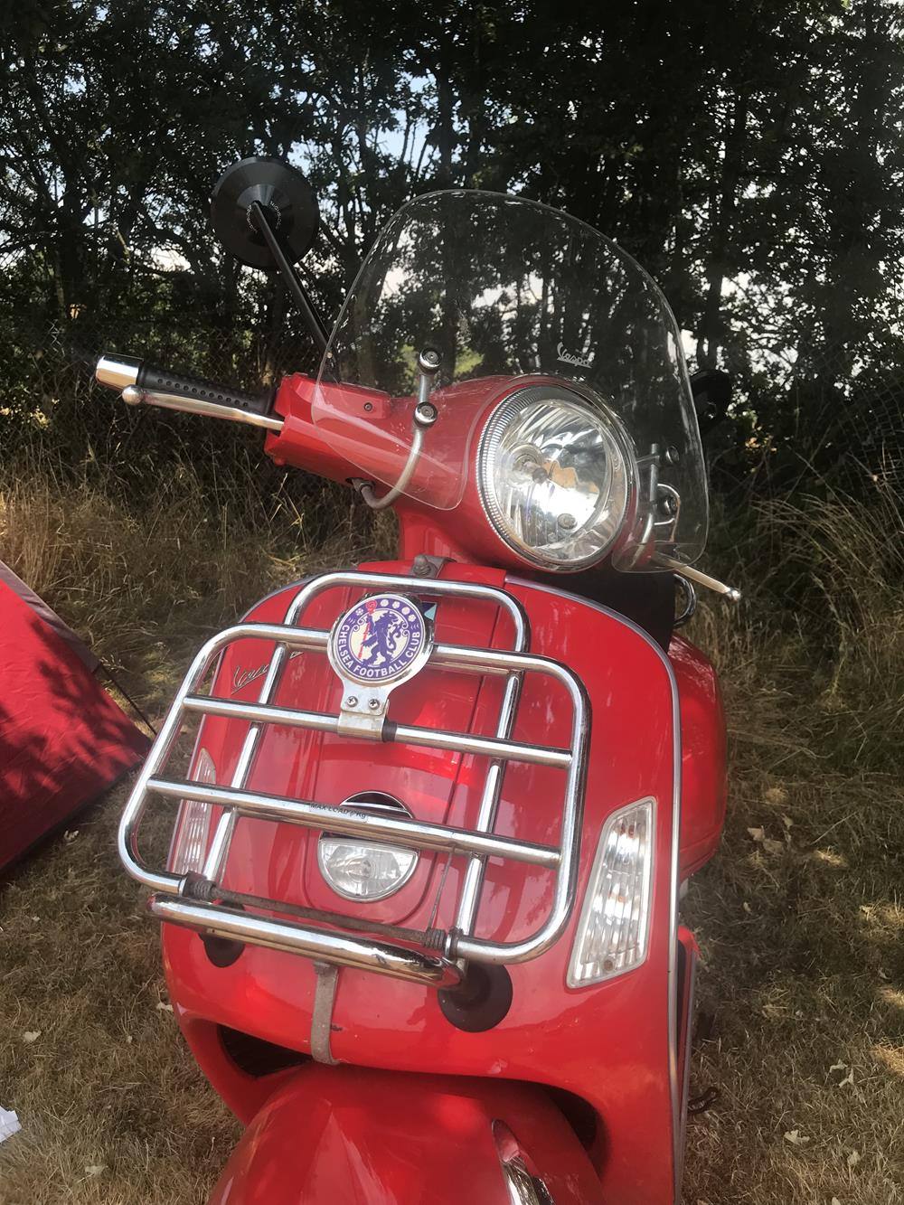 Red Vespa GTS with Chelsea fooball badge on the front rack