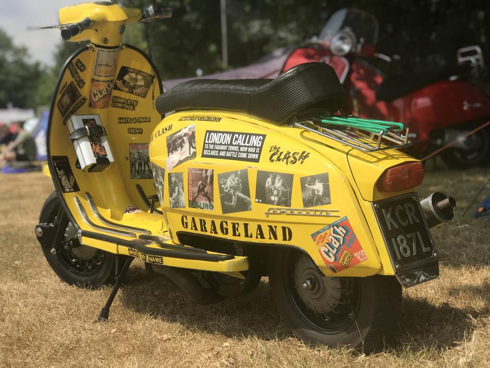 The Clash record covers on a yellow Lambretta