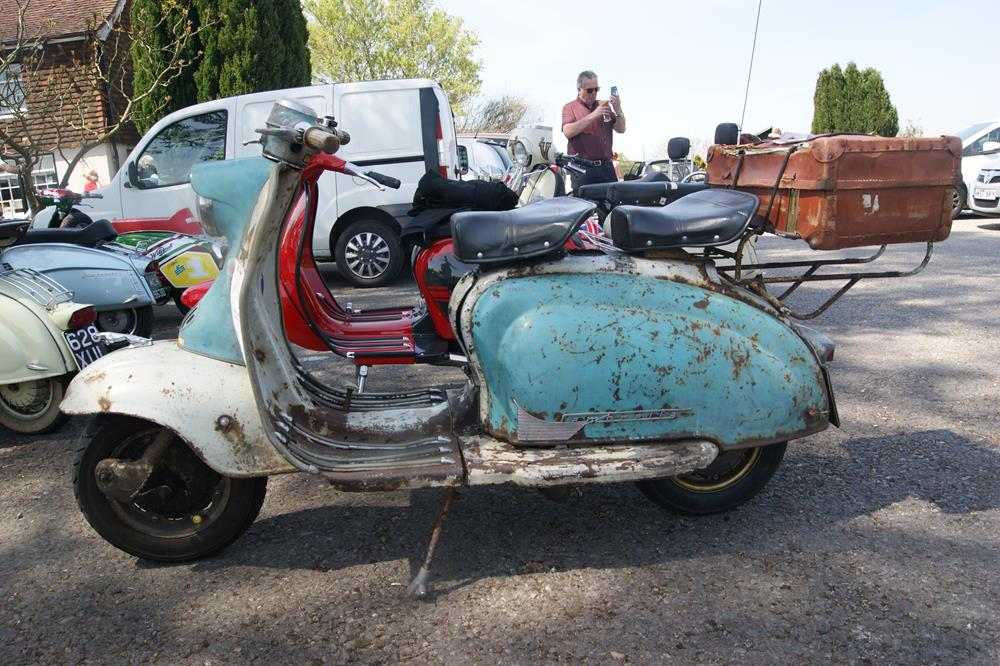 Rusty Lambretta with suitcase on the back rack