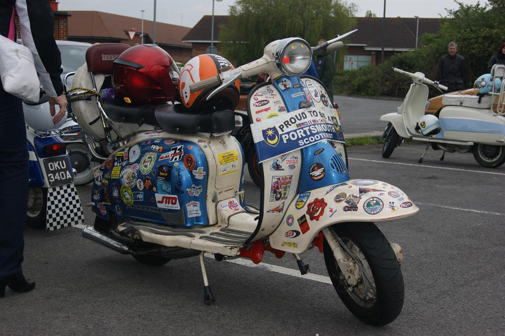 Lambretta scooter covered in stickers with Portsmouth scooterist legshield banner