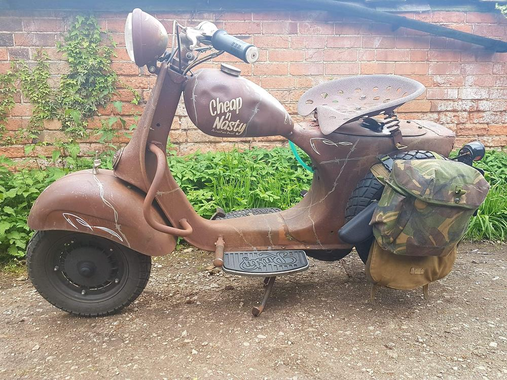 Side view of rusty Vespa with camouflage saddle bags and spare wheel