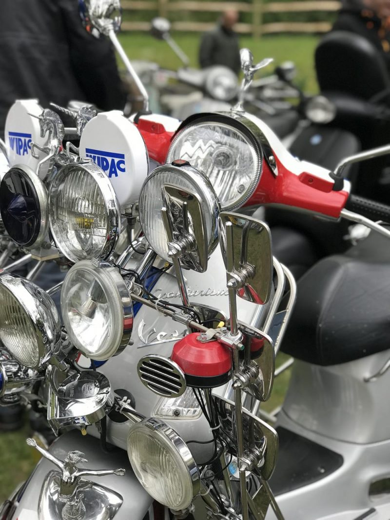 Closeup of Vespa GT front with lights and mirror accessories