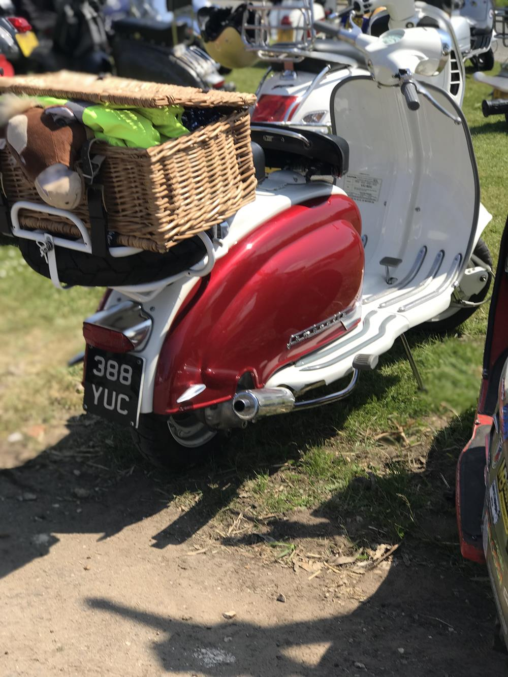 White Lambretta scooter with red side panels and picnic hamper basket on the back