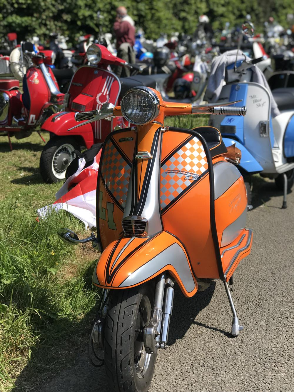 Orange LI Lambretta scooter with other scooters in the background