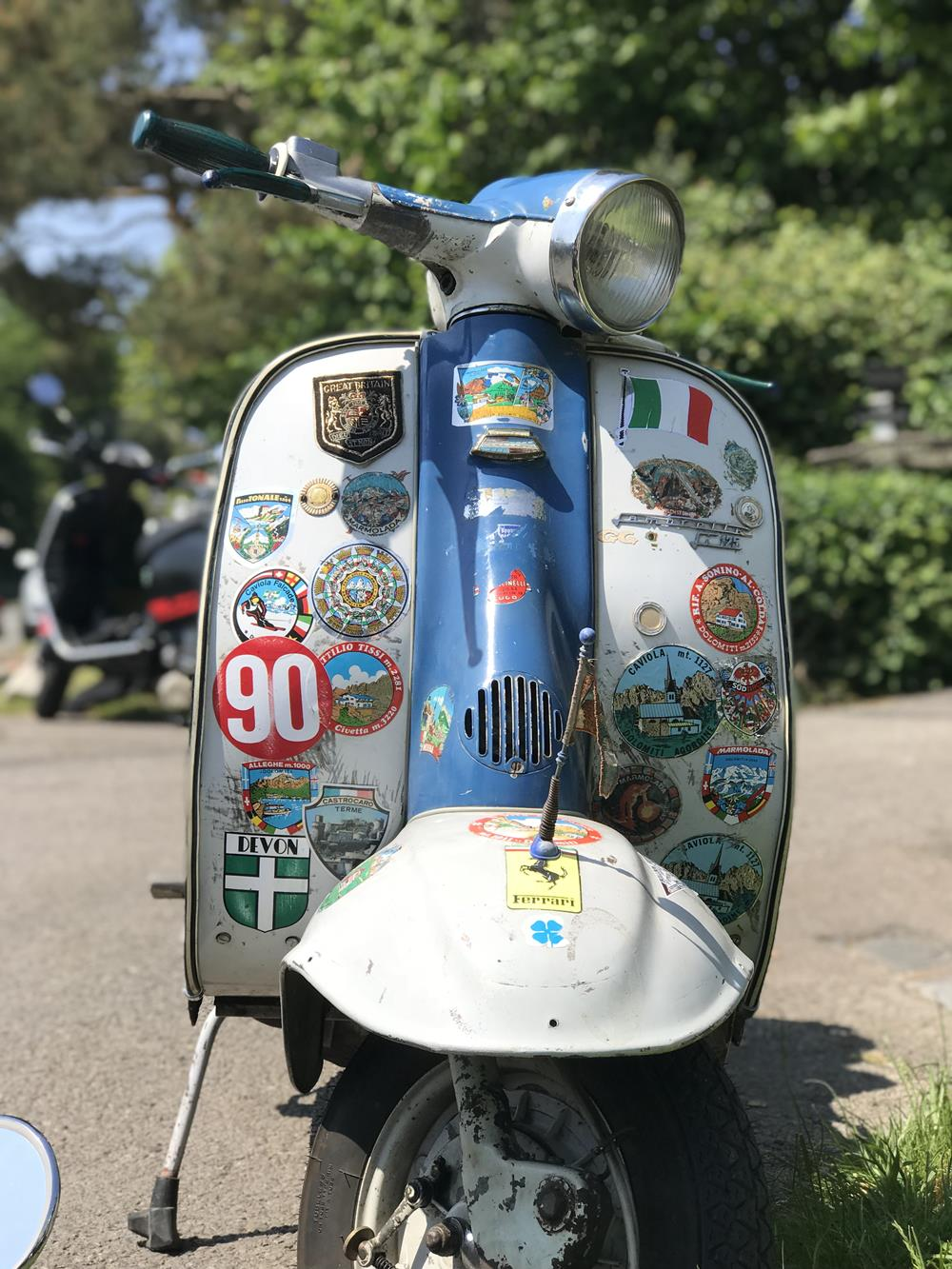 Rusty Lambretta scooter with stickers on the front fairing and a blue horncasting