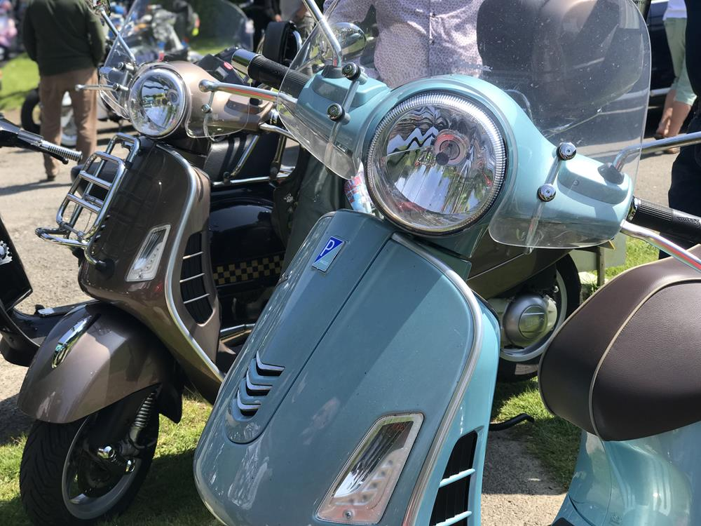 Turquoise Vespa GTS with black GTS in the background