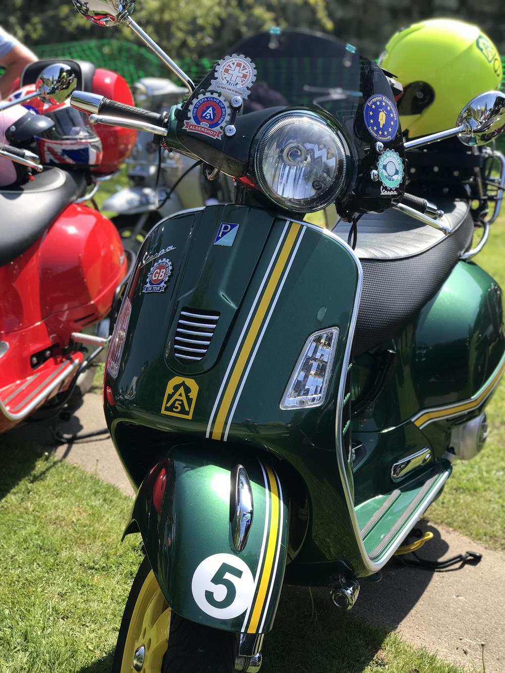 Green Vespa GTS scooter with yellow stripes and A5 scooter club stickers