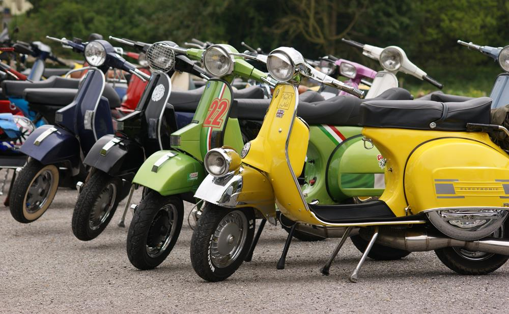 Colourful row of Vespas parked in a car park to illustrate scooter insurance tips