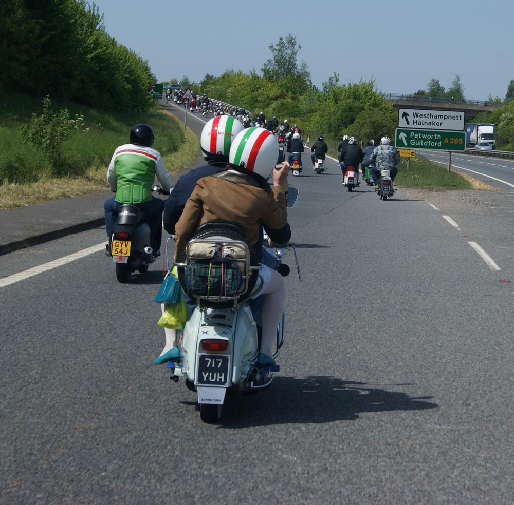 Riding behind a row of scooters on the road