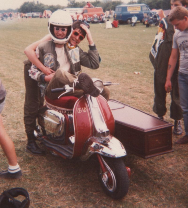 A red and Chrome Lambretta scooter with a sidecar shaped like a coffin, with a scooterboy sitting on it.
