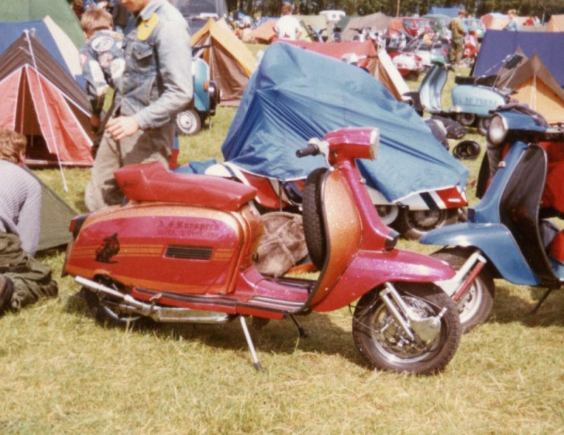 A red and orange painted custom Lambretta scooter with red seat, on a campsite with other scooters in the background