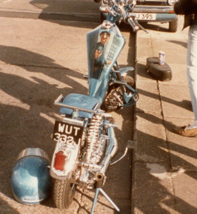 A blue Lambretta chopper with view of the petrol tank which has a skeleton pointing a gun at you.