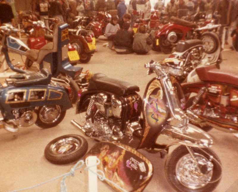 Lambretta surrounded by other custom scooters at a custom show