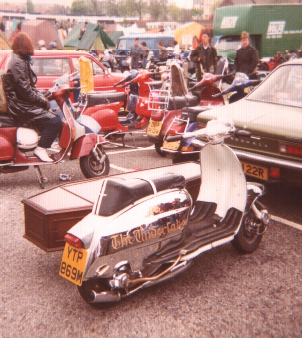 Chrome Lambretta with coffin sidecar and text The Undertaker on the side panel