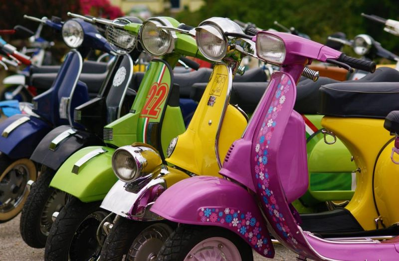 Row of colourful Vespas with pink Va Va Vroom in the foreground