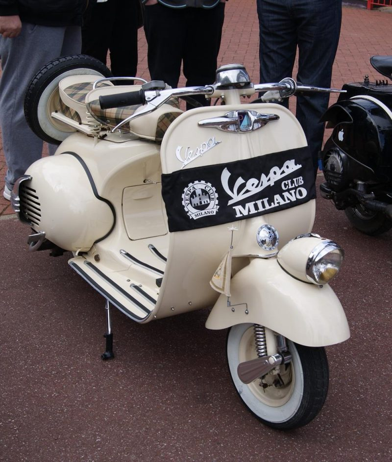 Cream vintage Vespa with Club Milano banner on the front legshields