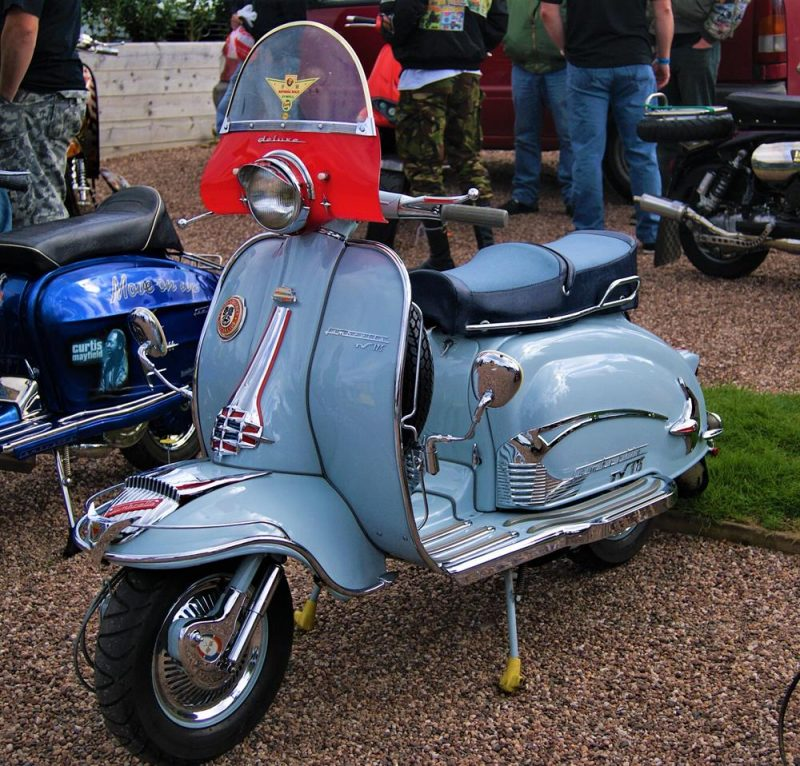 Vintage Lambretta with chrome embellishers on the side panels, mudguard and horn cover